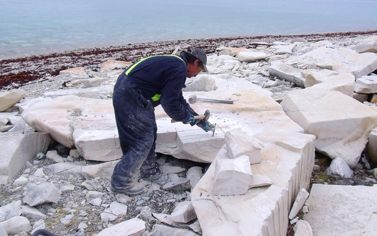 Carver Jerry Ell breaks out blocks of limestone on Bear Island, near Coral Harbour, Nunavut. Photo courtesy Government of Nunavut