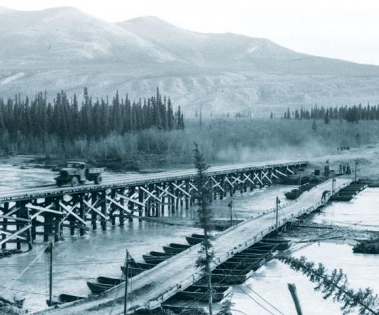 Permanent wood piles replace a temporary pontoon bridge on the Alaska Highway. Photo courtesy of Yukon Archives, R.A. Cartter fonds #1498