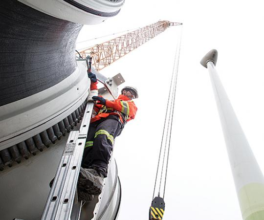 Workers erect one of the four 2.3-megawatt turbines now churning out energy at the Diavik diamond mine in the NWT. Photo courtesy of Rio Tinto (DDM)
